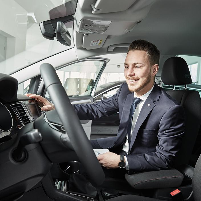 Verkäufer berät die Kunden beim Autokauf